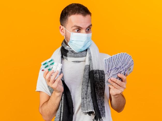Sorpreso giovane uomo malato che indossa cappello invernale e maschera medica tenendo le pillole e guardando i contanti in mano isolati su sfondo giallo