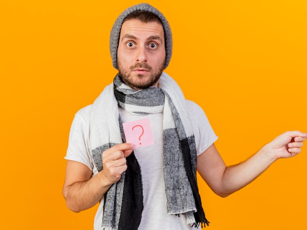 Surprised young ill man wearing winter hat and scarf holding question mark note and points at side isolated on yellow background