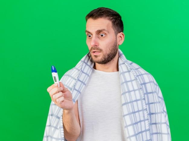 Удивленный молодой больной человек, завернутый в плед, держит и смотрит на термометр, изолированный на зеленом фоне