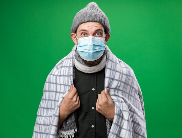 복사 공간이 있는 녹색 벽에 격리된 겨울 모자와 의료 마스크를 쓴 격자 무늬에 싸인 놀란 젊은 슬라브 남자