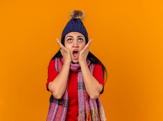 冬の帽子とスカーフを身に着けている驚いた若い病気の女性は、オレンジ色の壁に隔離された顔を見上げて手を維持します
