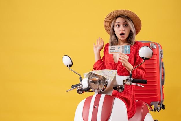 오토바이에 티켓을 들고 빨간 드레스에 놀란 된 아가씨