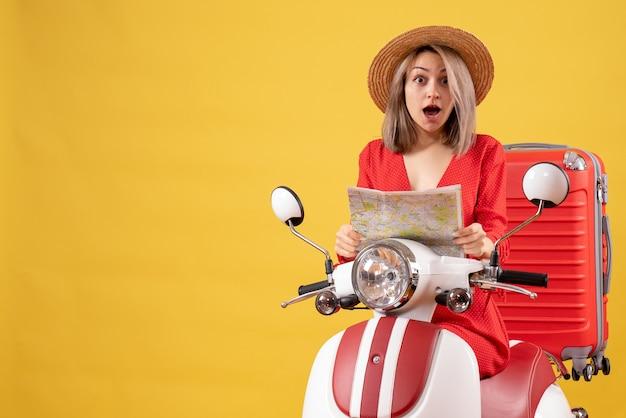 Удивленная молодая дама на мопеде с красным чемоданом держит карту