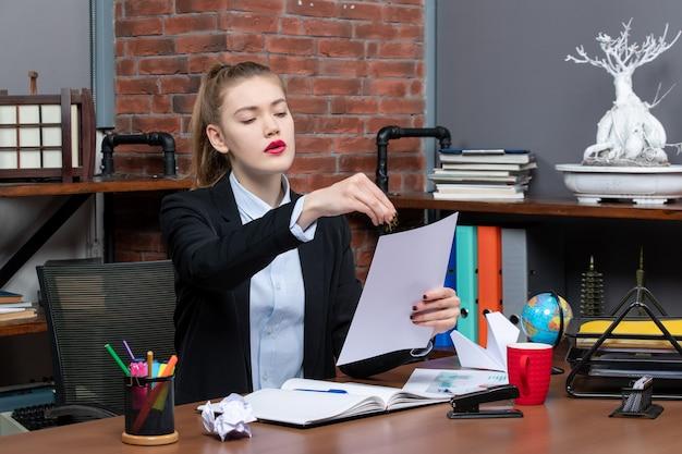 Sorpresa giovane donna seduta a un tavolo e leggendo i suoi appunti in un taccuino in ufficio