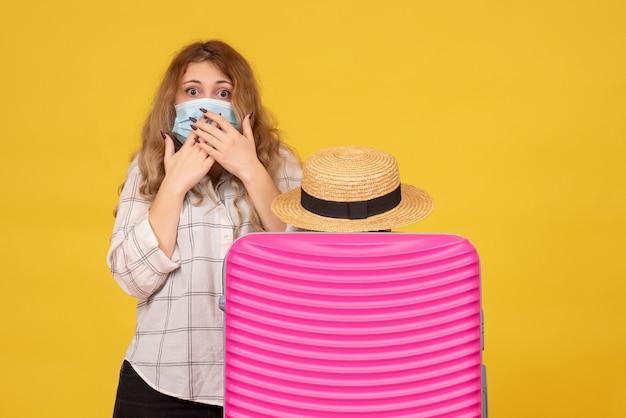 Giovane donna sorpresa che indossa la maschera che mostra il biglietto e in piedi dietro la sua borsa rosa