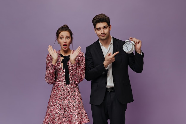 Surprised young lady with brunette hair posing in pink mini dress near pretty boy wearing black suit and showing time on clock