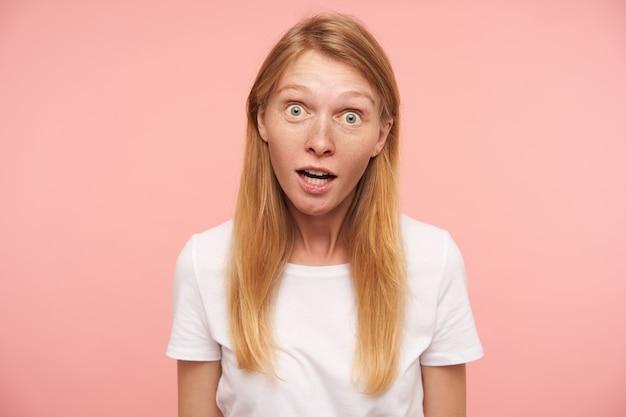 분홍색 배경 위에 서있는 넓은 눈을 가진 카메라를 궁금하게보고 자연스러운 메이크업으로 놀란 젊은 사랑스러운 긴 머리 빨간 머리 여성
