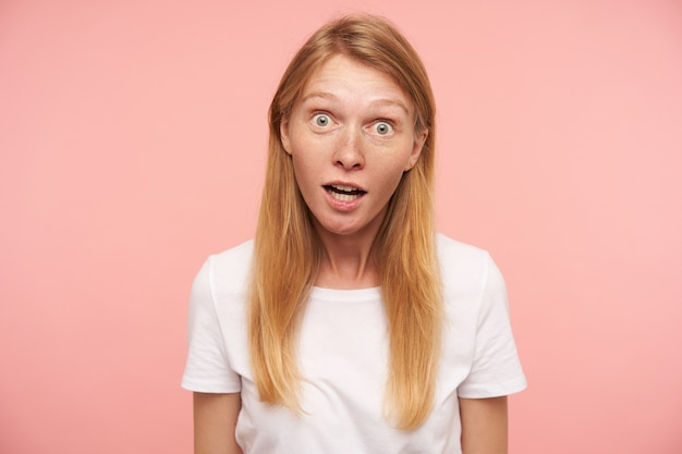 Surprised young lovely long haired redhead female with natural makeup looking wonderingly at camera with wide eyes opened, standing over pink background