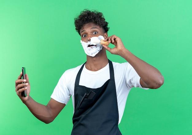 그의 얼굴에 면도 크림을 넣어 유니폼을 입고 놀란 젊은 남성 이발사