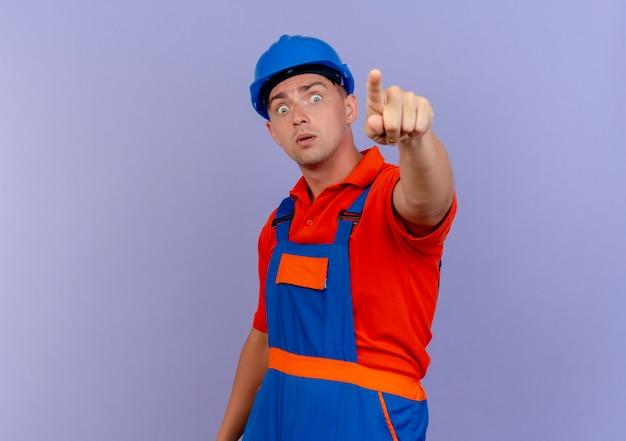 Удивленный молодой мужчина-строитель в униформе и защитном шлеме указывает на камеру на фиолетовом