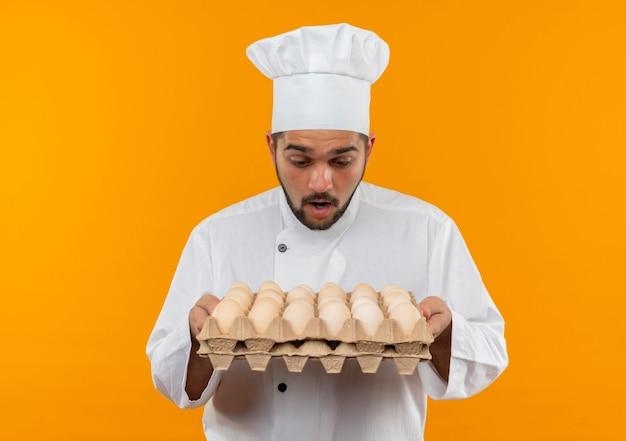 Giovane cuoco maschio sorpreso nella tenuta dell'uniforme del cuoco unico e nell'esame del cartone delle uova isolate sullo spazio arancio