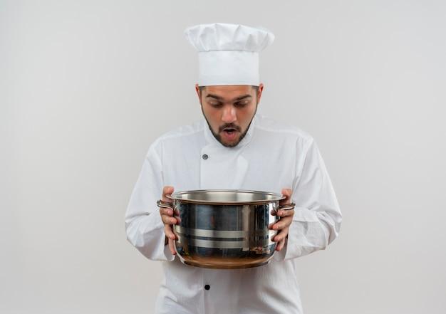 Giovane cuoco maschio sorpreso nella tenuta dell'uniforme del cuoco unico e che osserva dentro la pentola isolata su spazio bianco