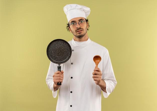 Giovane cuoco maschio sorpreso che indossa l'uniforme dello chef e bicchieri che tengono padella e cucchiaio