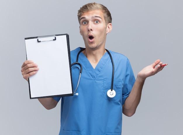 Giovane medico maschio sorpreso che indossa l'uniforme del medico con la lavagna per appunti della tenuta dello stetoscopio e la mano di diffusione isolata sulla parete bianca