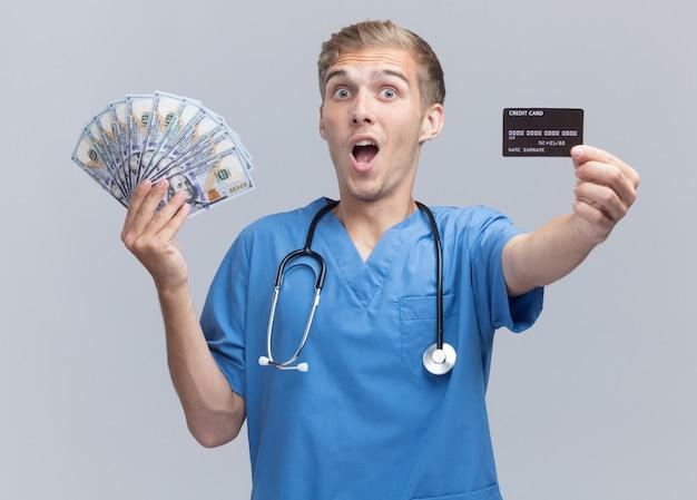 Giovane medico maschio sorpreso che indossa l'uniforme del medico con lo stetoscopio che tiene fuori contanti e carta di credito isolata sulla parete bianca