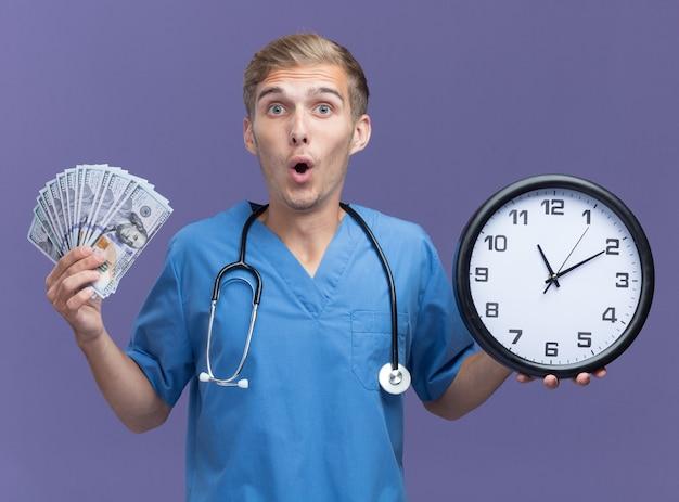 Giovane medico maschio sorpreso che indossa l'uniforme del medico con lo stetoscopio che tiene l'orologio da parete con contanti isolato sulla parete blu
