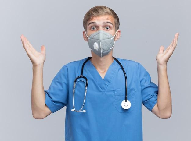 Giovane medico maschio sorpreso che indossa l'uniforme del medico con lo stetoscopio e la mascherina medica che diffondono le mani isolate sulla parete bianca