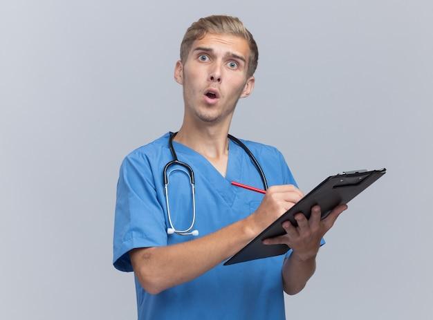 Giovane medico maschio sorpreso che indossa l'uniforme del medico con lo stetoscopio che scrive qualcosa sugli appunti isolato sulla parete bianca