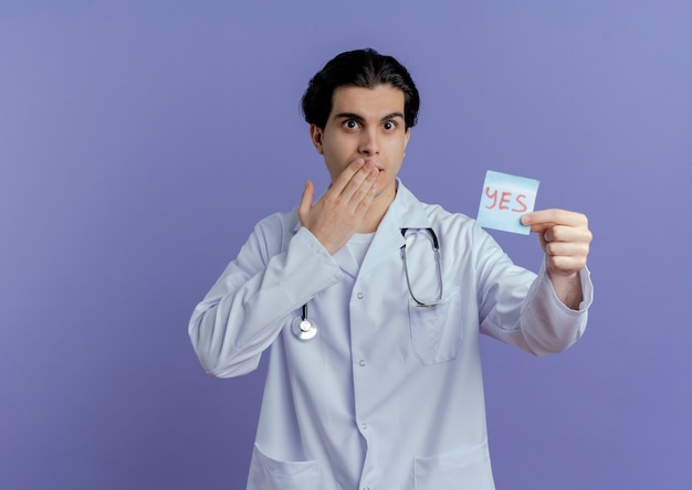 Surprised young male doctor wearing medical robe and stethoscope showing yes note  keeping hand on mouth isolated on purple wall with copy space