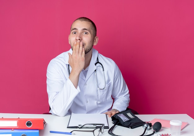 Surprised young male doctor wearing medical robe and stethoscope sitting at desk with work tools putting hand on mouth isolated on pink wall