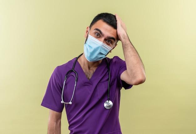Il giovane medico maschio sorpreso che indossa l'abbigliamento viola del chirurgo e la mascherina medica dello stetoscopio ha messo la sua mano sulla testa sulla parete verde isolata