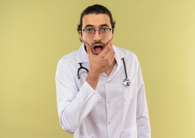 Giovane medico maschio sorpreso con vetri ottici che indossa una veste bianca con lo stetoscopio che mette la mano sul mento sulla parete verde isolata con lo spazio della copia
