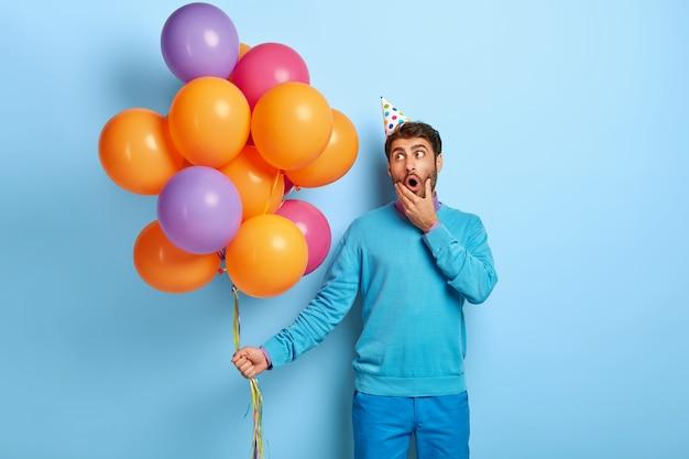 Il giovane manager di eventi maschio sorpreso tiene la bocca ben aperta, posa con un accessorio festivo