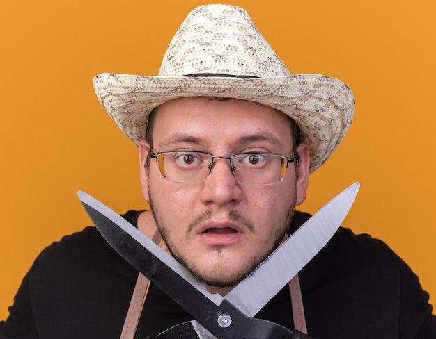 オレンジ色の壁に隔離された顔の周りにバリカンを保持しているガーデニング帽子と手袋を身に着けている驚いた若い男性の庭師