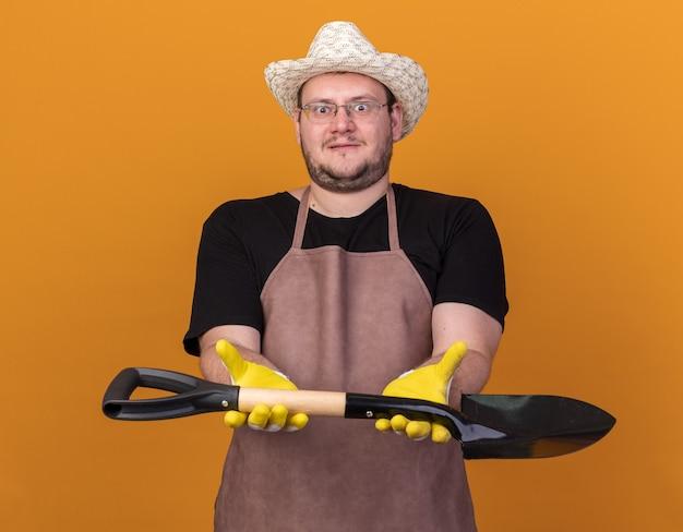 Удивленный молодой мужчина-садовник в садовой шляпе и перчатках протягивает лопату перед камерой, изолированной на оранжевой стене