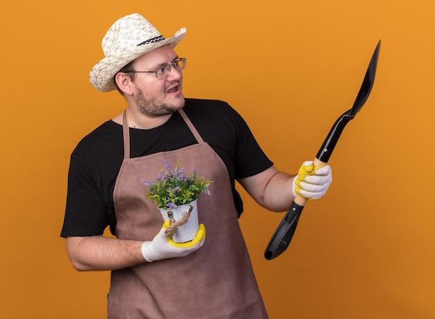 オレンジ色の壁に隔離された植木鉢に花を持って彼の手でスペードを見てガーデニング帽子と手袋を身に着けている驚いた若い男性の庭師