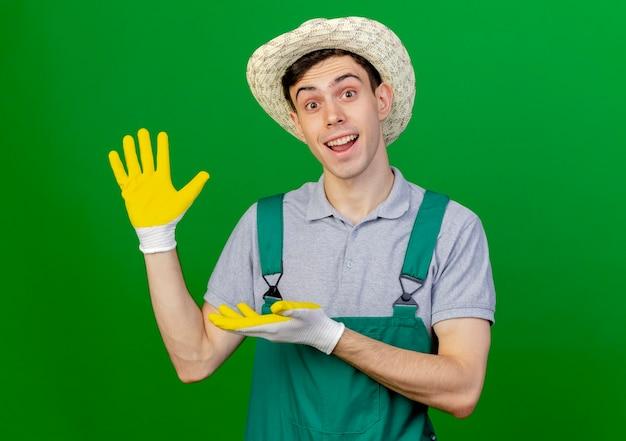 ガーデニング帽子と手袋を身に着けている驚いた若い男性の庭師は、コピースペースで緑の背景に分離された空の手でポイント