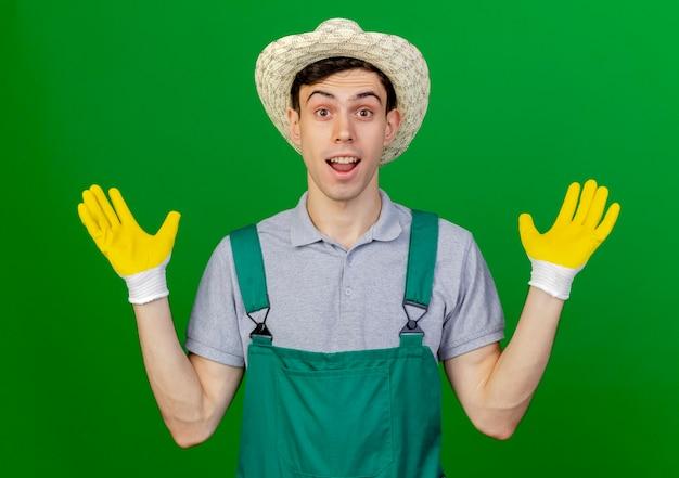Il giovane giardiniere maschio sorpreso che indossa guanti e cappello da giardinaggio sta con le mani alzate isolate su fondo verde con lo spazio della copia