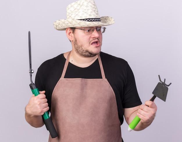 Giovane giardiniere maschio sorpreso che indossa il cappello di giardinaggio che tiene i clippers e che esamina il rastrello della zappa nella sua mano isolata sulla parete bianca