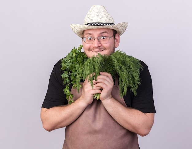 Surprised young male gardener wearing gardening hat holding dill with cilantro around face isolated on white wall