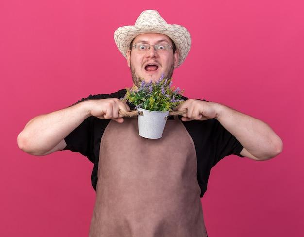 ピンクの壁に隔離植木鉢に花を保持しているガーデニング帽子をかぶって驚いた若い男性の庭師