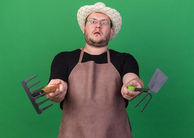녹색 벽에 고립 된 카메라에서 괭이 갈퀴와 갈퀴를 들고 원예 모자를 쓰고 놀란 젊은 남성 정원사