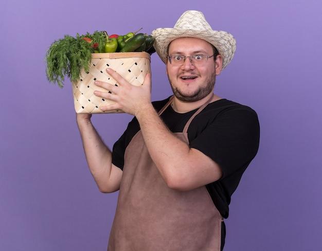Giovane giardiniere maschio sorpreso che indossa il cappello di giardinaggio che tiene il cestino della verdura isolato sulla parete blu