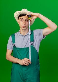 ガーデニング帽子をかぶって驚いた若い男性の庭師は、コピースペースで緑の背景に分離された巻尺を保持します。