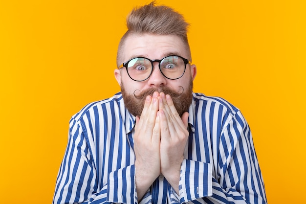 Surprised young male hipster with glasses embarrassed covers his mouth and laughs posing on a yellow