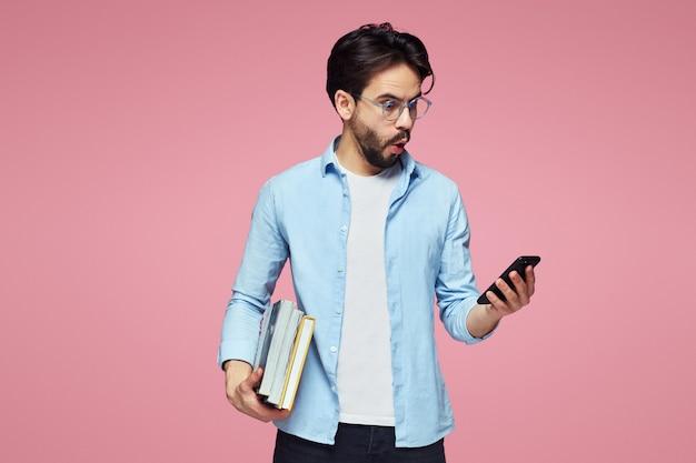 Удивленный молодой мужчина держит мобильный телефон и книги на розовом фоне
