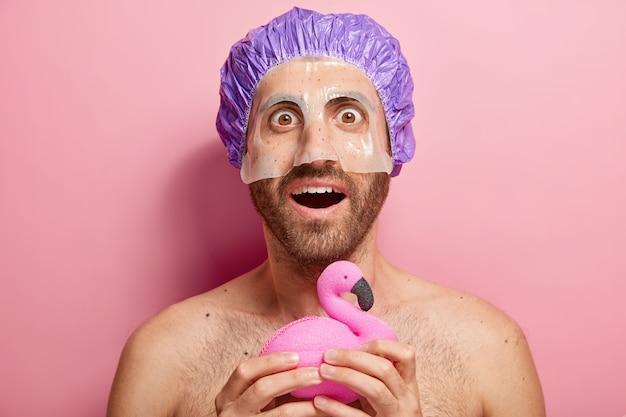 Il giovane sorpreso applica la maschera cosmetica tiene la spugna da bagno a forma di fenicottero, indossa il cappuccio della doccia, ha una routine igienica, sta con il torso nudo