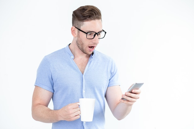 Surprised young man in glasses using smartphone