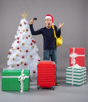 Surprised young man holding card standing near xmas tree and presents on grey