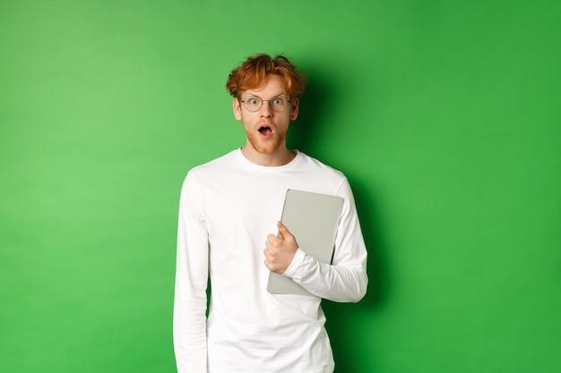 노트북을 들고 카메라를 쳐다보고 안경과 흰색 티셔츠를 입고, 녹색 배경 위에 서 놀란 젊은 남자.