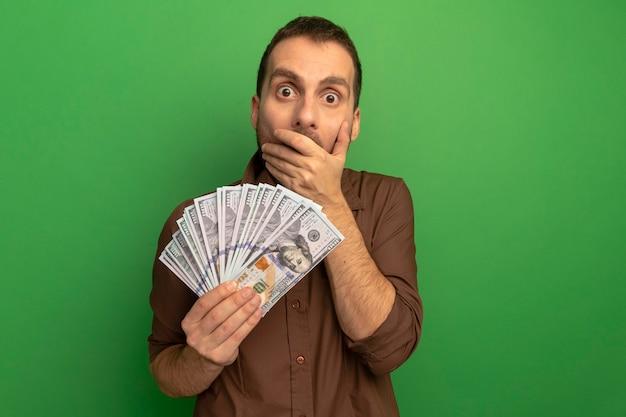 Giovane sorpreso che tiene i soldi che esaminano davanti mettendo la mano sulla bocca isolata sulla parete verde