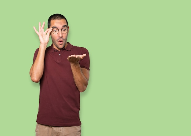 Удивленный молодой человек, держащий что-то рукой