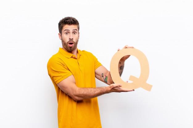 Удивленный молодой человек держит букву q