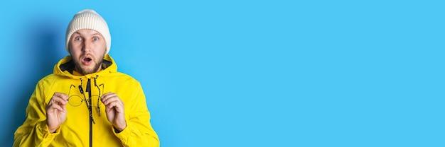 青い背景に彼の手で眼鏡を保持している黄色のジャケットで驚いた若い男。バナー。