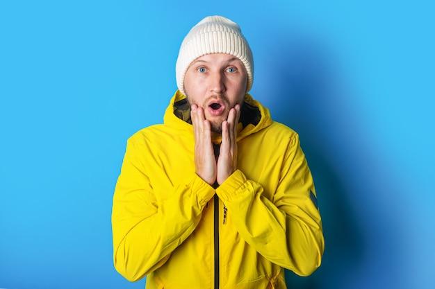 青い背景に彼の手のひらで彼のあごを保持している黄色のジャケットで驚いた若い男。