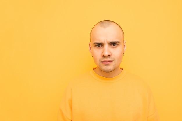 黄色のコートを着た驚いた若い男がオレンジの上に立ち、ショックを受けた顔でカメラを見ます。